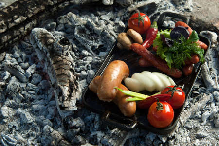smoked sausages and tomatoes lie on charcoal. the dish is cooked and smoked on charcoal Stock Photo