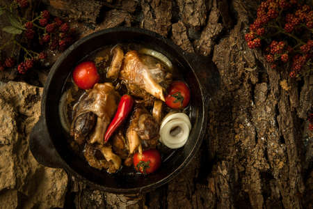tomate de arbol: chicken dish with vegetables in a frying pan on the background of tree bark