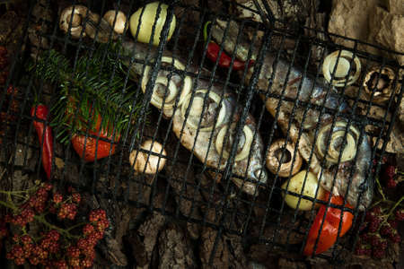 grille: smoked fish with vegetables and pine branches on a background of tree bark Stock Photo