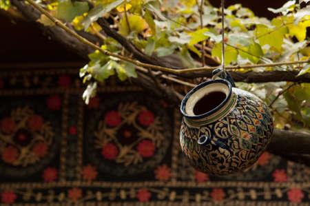 an oriental-style teapot is hanging on a tree branch on a carpet background
