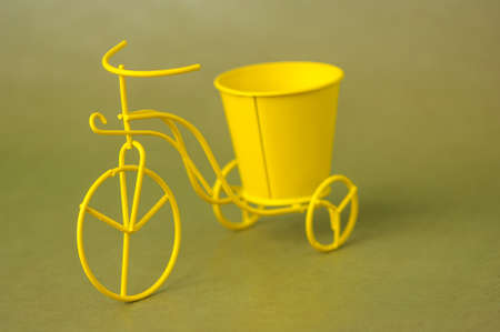 souvenir toy metallic bicycle with a bucket on a dark green background