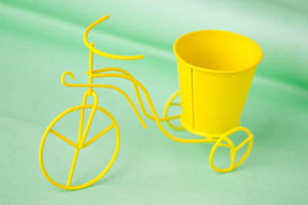 souvenir toy metallic bicycle with a bucket on a green background Stock Photo
