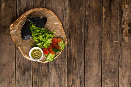 vegetarian hamburger: sandwich of black bread with vegetables on a wooden surface