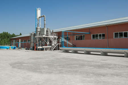 industrial one-story building with tanks and irrigation ditch Stock Photo
