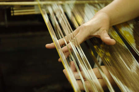 weaving and manufacturing of handmade fabric close up. womens hands behind a loom make cloth Stock Photo