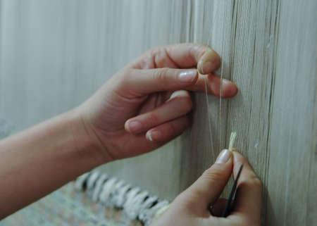 Tessitura e produzione di tappeti fatti a mano primo piano. le mani delle donne intrecciano un tappeto Archivio Fotografico - 83795642