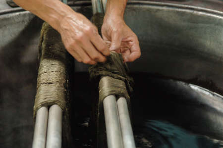 painting threads and yarns. male hands paint the cloth in the trough
