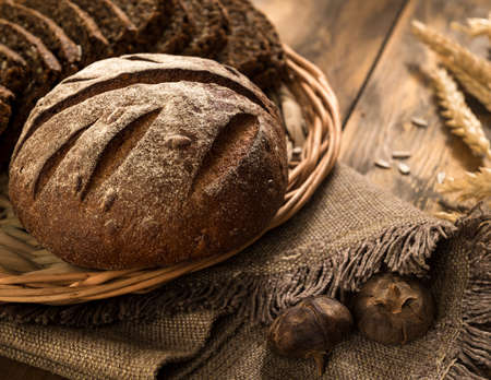 round rye bread in a wicker tray with a napkin and spikelets on wooden surface