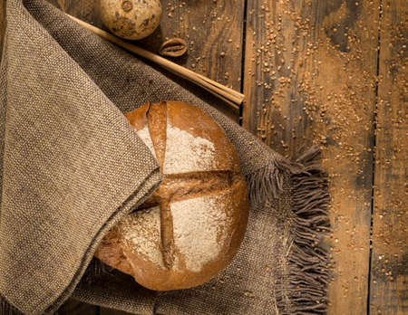 round loaf of bread on a cloth napkin and wooden boards with crumbs Stock Photo