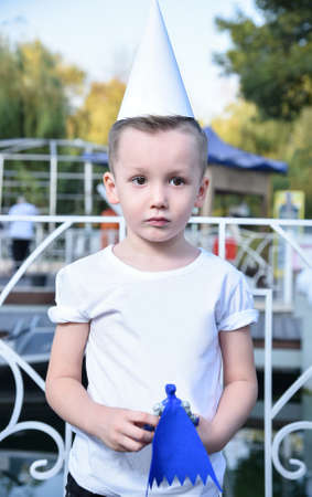 portrait of a sad little boy with a toy in his hand and the conical hat in the Park Stock Photo
