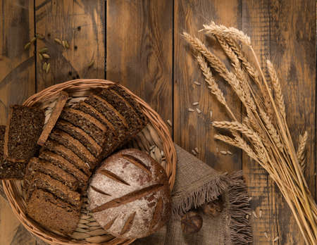 Sliced bread in a wicker tray with spikelets wooden surface with cloth