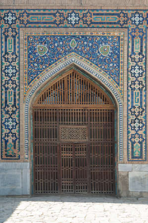Wooden door with ancient traditional Asian ornamentation and mosaics. The details of the architecture of medieval Central Asia Stock Photo