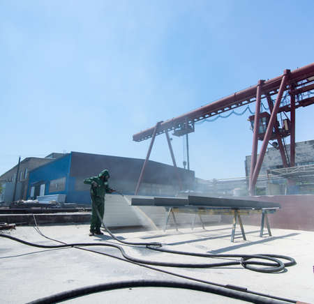 Factory for cleaning of metal by sandblasting. the worker performing the cleaning by sandblasting of metal structures Stock Photo
