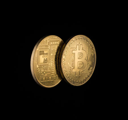 two Golden bitcoins on black background with copy space. electronic money isolated