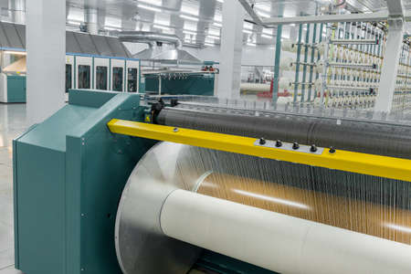 textile yarn on the wrapping machine is screwed on the big shaft. machinery and equipment in a textile factory