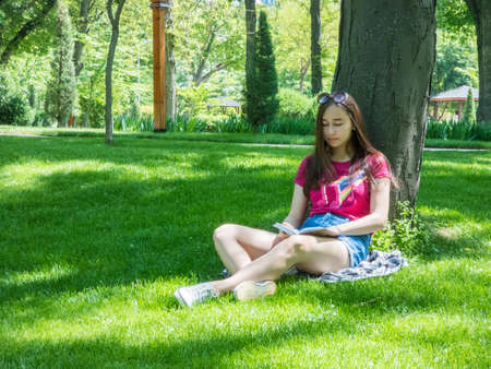 young girl reading a book in a picturesque park, sunny day. the girl of Asian appearance Stock Photo
