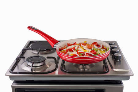 vegetables in a frying pan are cooked on modern electric stove. kitchen equipment