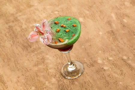 Green smoothie on a light brown background