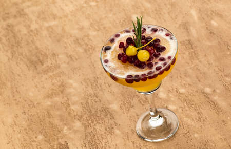 Yellow fruit cocktail with berries on light brown background