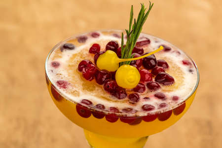 Yellow fruit cocktail with berries on light brown background, close up Reklamní fotografie