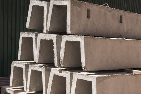 New concrete blocks for drainage, stacked in a row. Building material