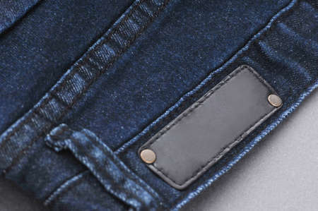 part of denim pants with back pockets and label, close-up