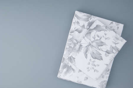 folded new bed linen with patterns on grey background, top view