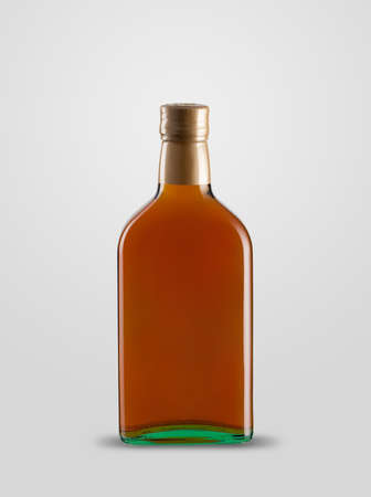 one closed bottle of cognac on white background with shadow