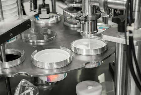 producción y envasado de yogur en vasos de plástico. equipo en la planta de productos lácteos Foto de archivo
