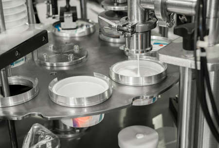 produzione e imbottigliamento di yogurt in bicchieri di plastica. attrezzature presso lo stabilimento lattiero-caseario Archivio Fotografico