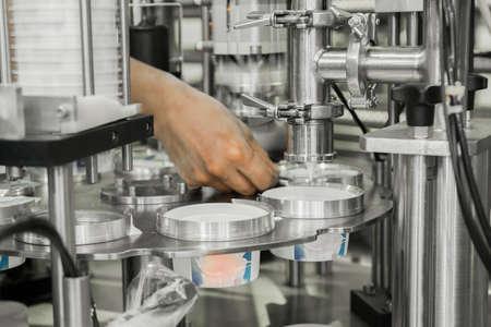 Herstellung und Abfüllung von Joghurt in Plastikbecher. Ausrüstung in der Molkerei Standard-Bild