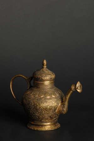 ancient oriental metal teapot on dark background. antique bronze tableware Reklamní fotografie