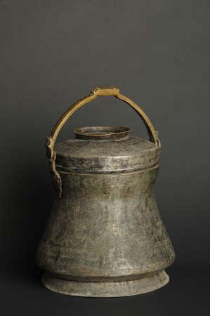 ancient metal bowl on dark background. antique bronze tableware Standard-Bild