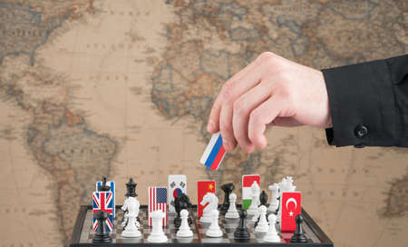 Politician's hand moves a chess piece with a flag. Conceptual photo of a political game. retaliatory move of Russia