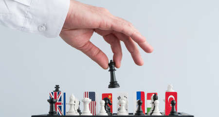 Politicians hand moves a chess piece. Conceptual photo of a political game and strategy.