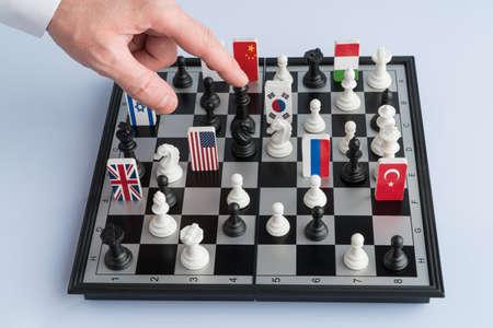 La mano del político mueve una pieza de ajedrez. Fotografía conceptual de un juego político y de estrategia. Foto de archivo