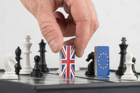 Hand policy raises the figure with the flag of Britain. The concept of political game and chess strategy Brexit 版權商用圖片 - 121990018
