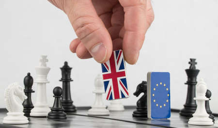 Hand policy raises the figure with the flag of Britain. The concept of political game and chess strategy Brexit