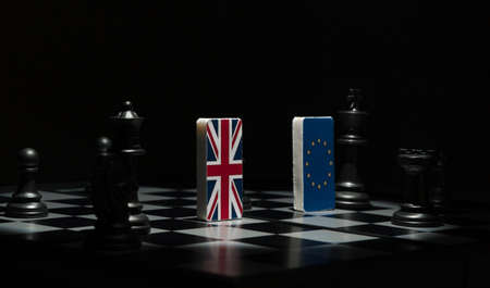 Backlit in the shadows figures and flags of the European Union and Great Britain on the chessboard. The concept of the political game and chess strategy Brexit