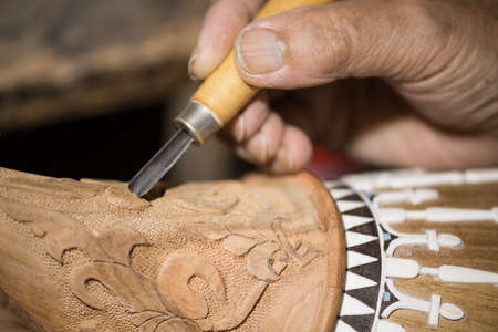adult master restores old musical instruments. wood carving