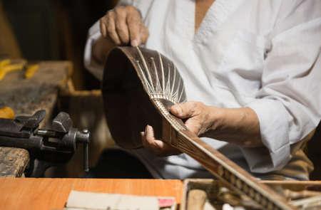 erwachsener Meister restauriert alte Musikinstrumente. Herstellung von Saiteninstrumenten