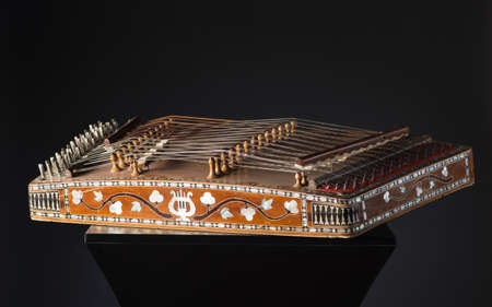 ancient Asian stringed musical instrument on black background with backlight. the similarity of the harp and psaltery