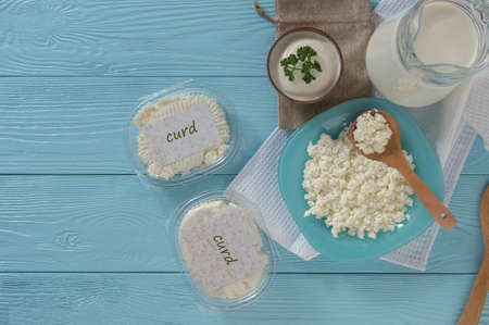 Cottage cheese in plastic packaging and milk on a wooden blue background, top view. healthy eating concept
