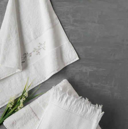 soft towel with a flower in a grey  decorative stucco background. top view, isolated Standard-Bild - 121991974
