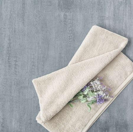 toalla suave con una flor sobre un fondo de estuco decorativo gris. vista superior, aislado