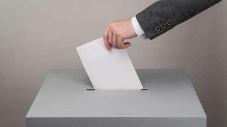 Urne grise. Élections présidentielles et législatives. L'électeur jette son bulletin dans l'urne. Banque d'images