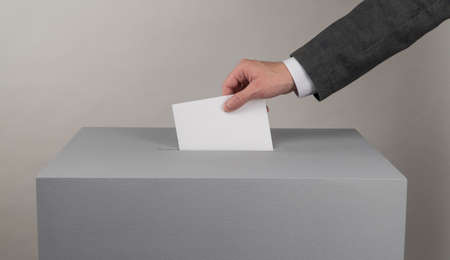 Gray ballot box. Presidential and parliamentary elections. The voter throws the ballot into the ballot box. Banque d'images