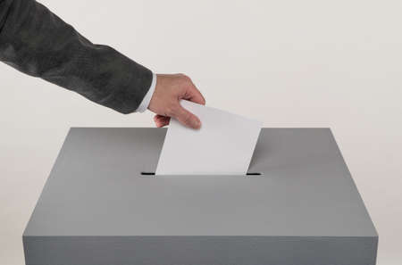 Gray ballot box. Presidential and parliamentary elections. The voter throws the ballot into the ballot box. 免版税图像