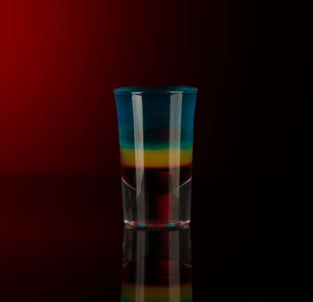 mixed alcoholic liquor in a shot glass isolated on a red background with backlighting