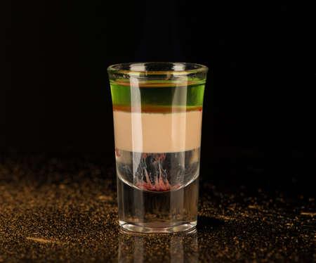 Liquore alcolico misto con cannella in un bicchierino isolato su sfondo nero Archivio Fotografico